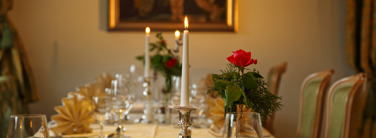 Long table decorated with red roses and candles lit