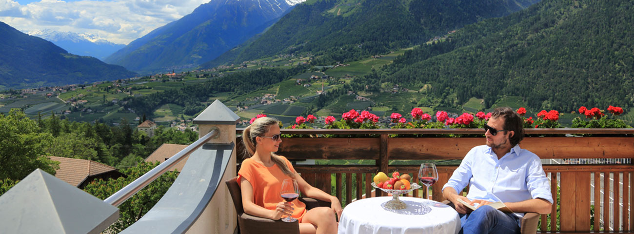 Man and woman sitting at a table on the terrace of the Hotel Grafenstein, chatting