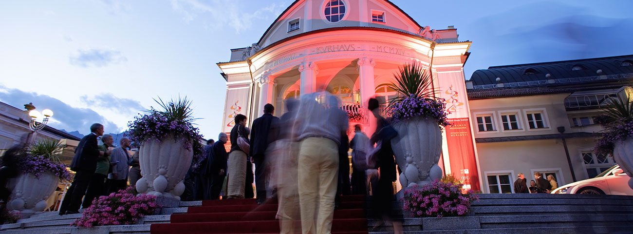 People who enter the Kurhaus Merano for a concert: A Baroque building in white masonry