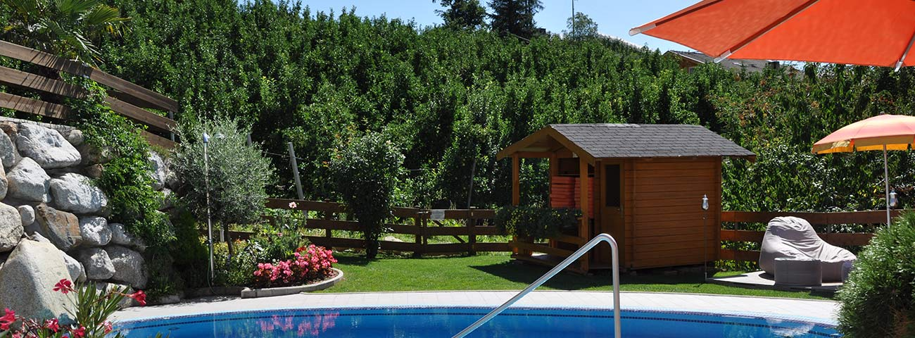 Garden with cabin, umbrellas and pool