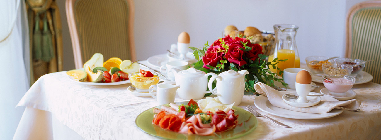 Table set for breakfast with ham, eggs, juice, milk and more