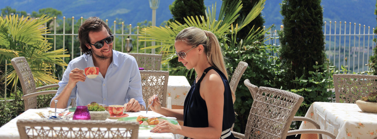 Man and woman during an outdoor lunch on the terrace of Grafenstein near Merano