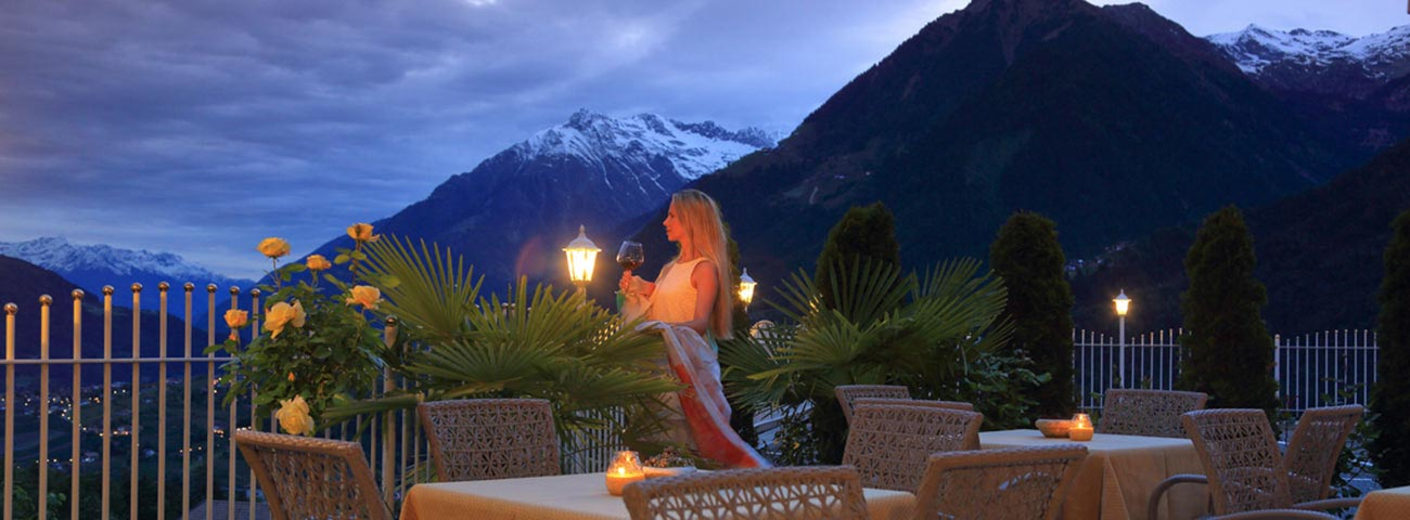 Woman in the evening on the terrace of Hotel Grafenstein is looking at snowy mountains