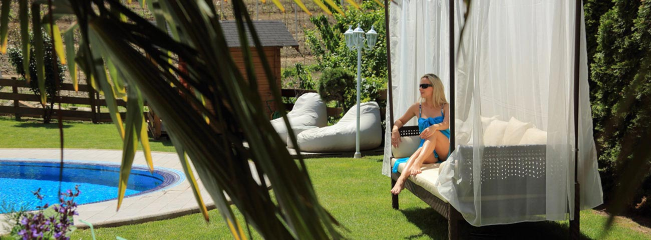 Blond woman with sunglasses and blue dress sitting on a bench by the pool