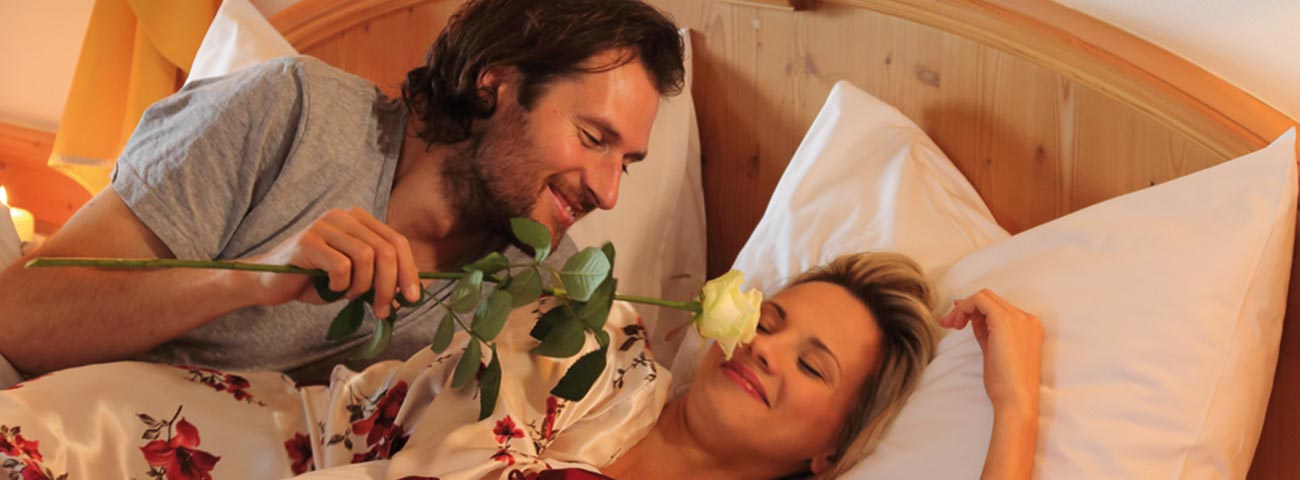 Man tickles with a white rose to the woman who has just woken up