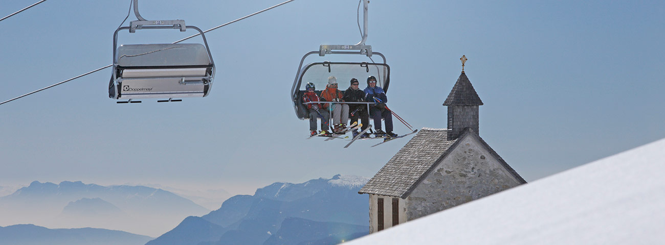 Chairlift with four people on board passes next to a church in the middle of the snowy mountains