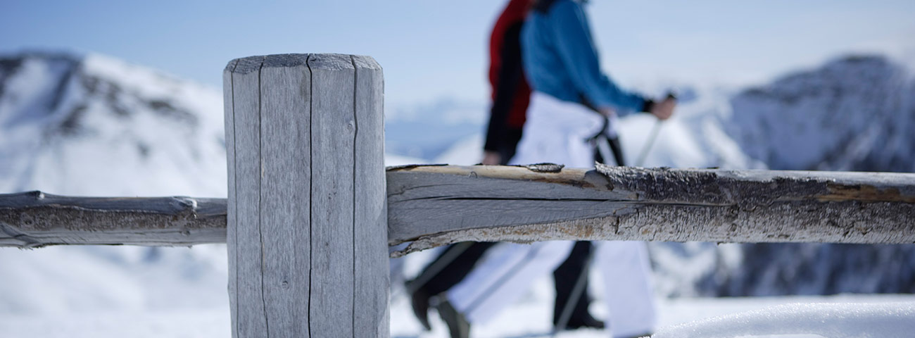 Closeup of a fence, and focus in the background, two people walking on the snow