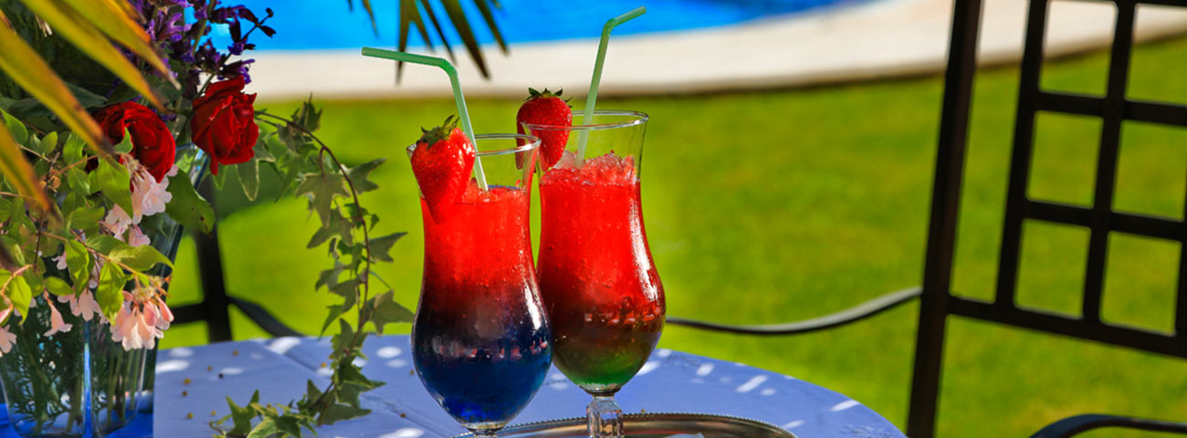 Two strawberry cocktail on a small blue table in the garden of  Grafenstein Hotel Scena