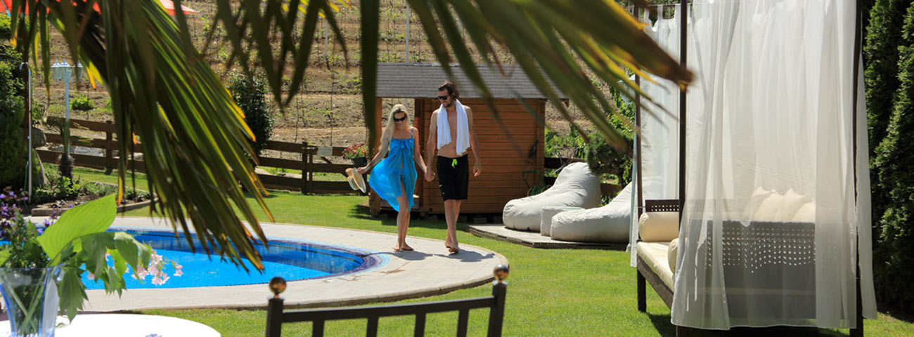 Woman with blue sunskirt and man with a towel around his neck walking poolside
