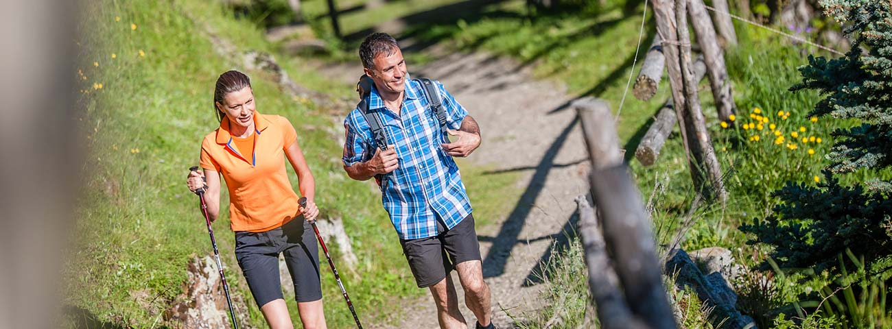 Pair of hikers walking along a path near a wooden fence
