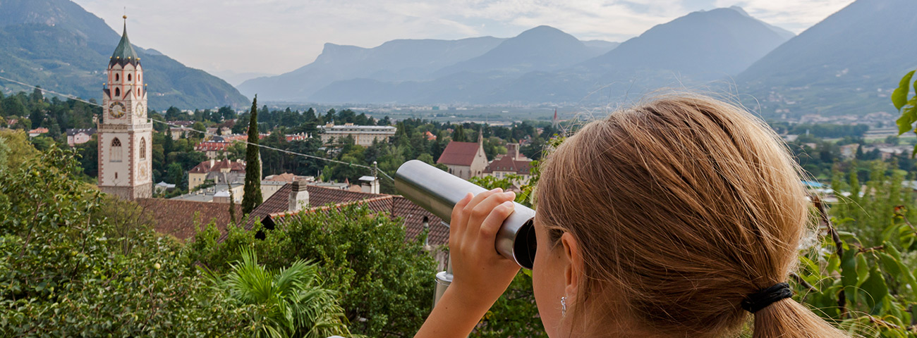 Little blond girl looks with monocle at Merano in the distance