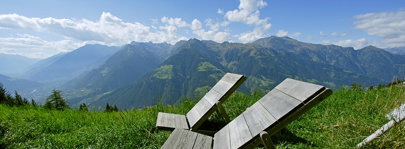Two wooden deck chairs from which you can admire the view of Merano and surroundings