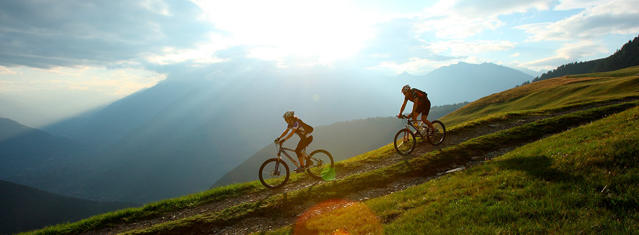 Two cyclists driving their mountain bike downhill at sunset