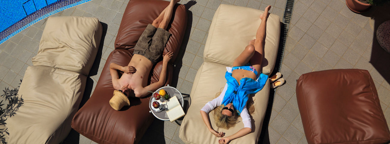 A couple relaxes on the sun loungers by the pool with a basket of fruit