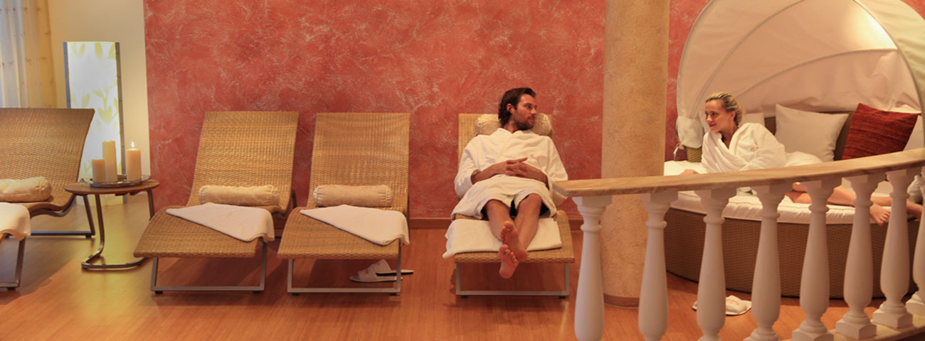 Man and woman in white bathrobe relax in the relaxation area of the Hotel Grafenstein 4 stars