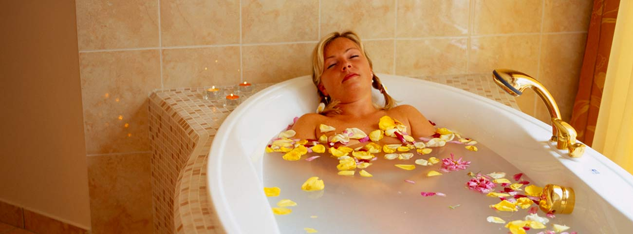 Woman with braids in bathtub full of water and flower petals