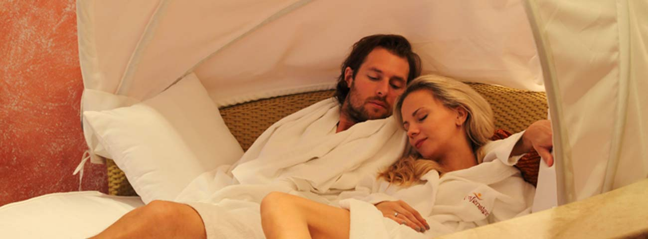 Couple in white bathrobe relaxes lying on a mattress in the relaxation area
