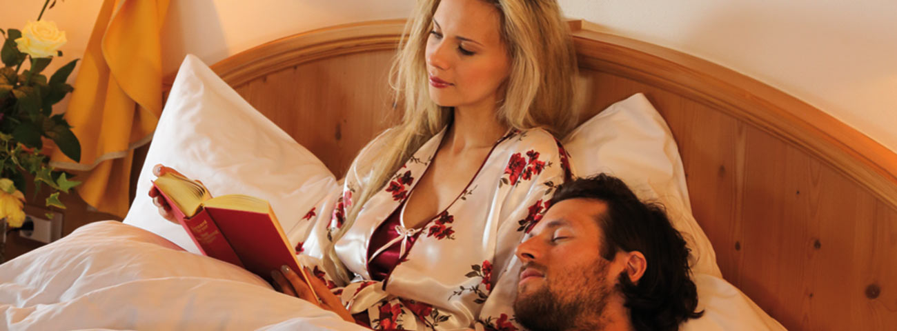 Blonde woman in robe reading a book in bed while your partner sleeps next to her