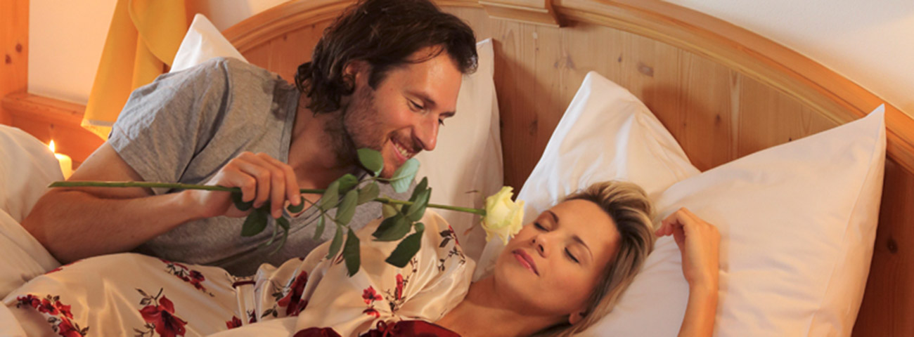 Man wakes their loved up, making her smell a white rose